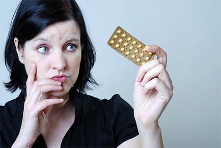 birthcontrol-woman-looking-at-pills-450x300