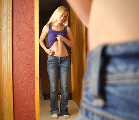 dietharm-woman-looking-in-mirror-purple-tanktop-450x388
