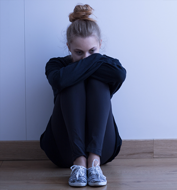 sad-woman-on-floor-hugging-knees-350x375