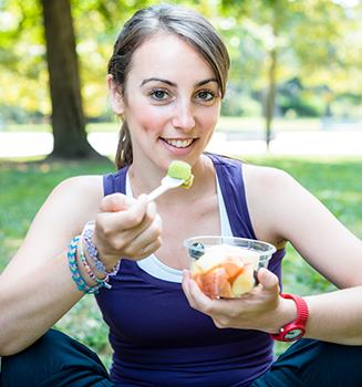 woman-eating-fruit-salad-outdoors-327x350